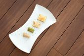 stock photo of baklava  - Variety of turkish baklava on a white porcelain plate - JPG