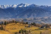 stock photo of hamlet  - Countryside mountain landscape with ancient remote Romanian hamlet in the wide valleys of Bucegi mountains Brasov county Romania - JPG