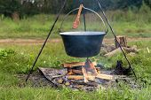picture of stew pot  - Camp fire outdoors burning with logs and pot - JPG
