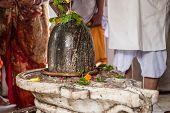 stock photo of lingam  - Hindu devotees bathe a shiva - JPG