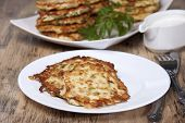 stock photo of zucchini  - Vegetable fritters of zucchini with parsley and dill closeup and sauceboat with sour cream - JPG