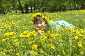 picture of dandelion  - European lady brunette in wreath of yellow dandelions laying on meadow with dandelions - JPG