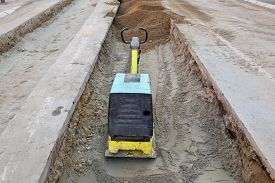 picture of vibration plate  - Vibratory plate compactor compacting sand at road construction site - JPG