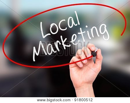 Man Hand writing Local Marketing with marker on transparent wipe board.