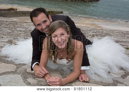 Newly Wedding Couple Laying On The Gound Outside