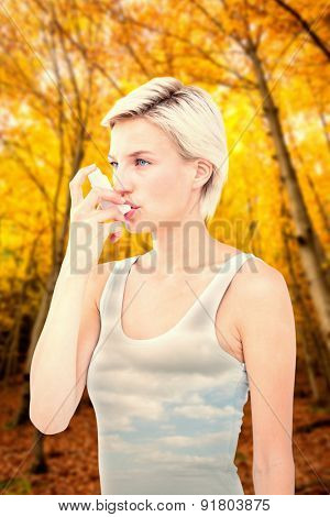 Blonde woman taking her inhaler against sky
