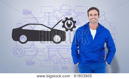 Happy mechanic with hands in pockets against grey vignette
