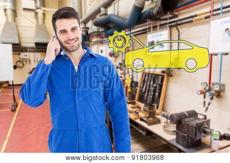 Smiling male mechanic using mobile phone against workshop