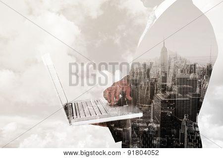 Businessman holding laptop against new york skyline