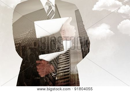 Businessman holding his laptop tightly against low angle view of skyscrapers
