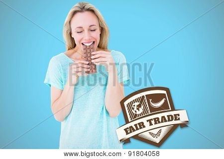Happy blonde eating bar of chocolate against blue background with vignette