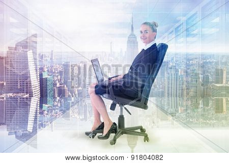 Businesswoman sitting on swivel chair with laptop against digitally generated server room with towers