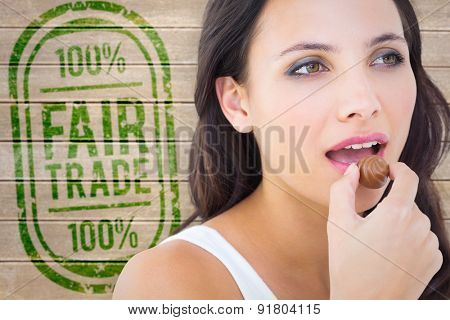 Pretty brunette eating chocolate candy against wooden surface with planks