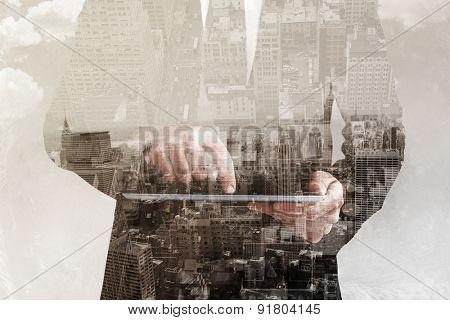 Businessman using his tablet pc against new york skyline