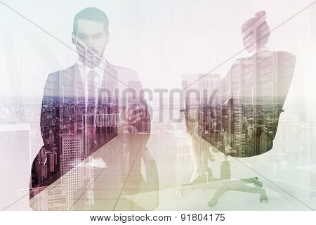 Serious businessman sitting with arms crossed against server room with towers
