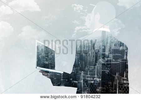 Businessman looking up holding laptop against new york skyline