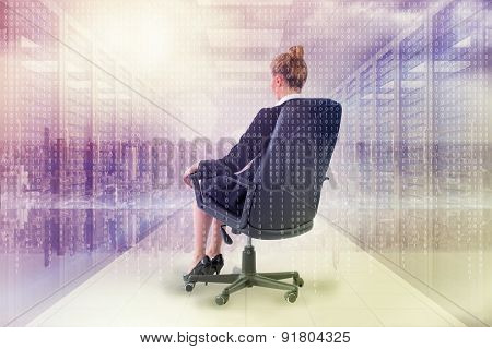 Businesswoman sitting on swivel chair in black suit against digitally generated server room with towers