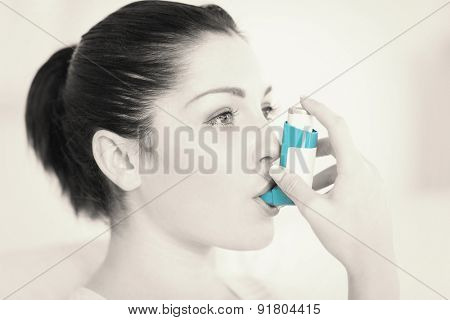 Woman having asthma using the asthma inhaler for being healthy