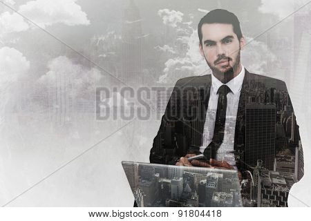 Cheerful businessman with laptop using smartphone against new york skyline