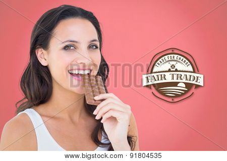 Pretty brunette eating bar of chocolate against red background