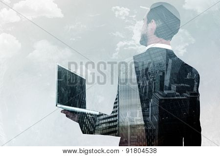 Businessman looking up holding laptop against low angle view of skyscrapers