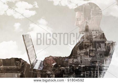 Businessman using laptop against new york skyline