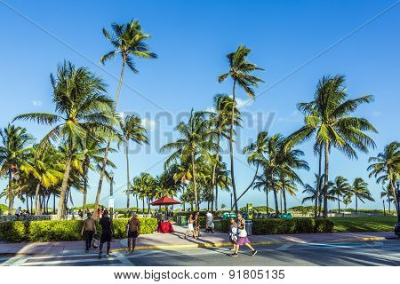 People Walk Along The Promenade At Ocean Drive