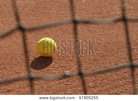 Tennis Ball Photo Through Blurred Tennis Net