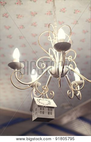 Vintage chandelier with small wooden decorative house on it