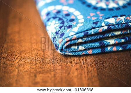 blue fabric textile with ornament on wooden background
