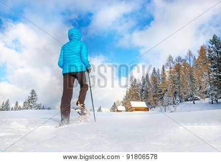 Young woman running with snow shoes in winter