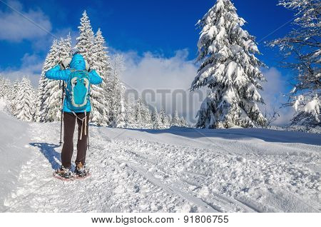 Young woman in blue jacked on winter trail