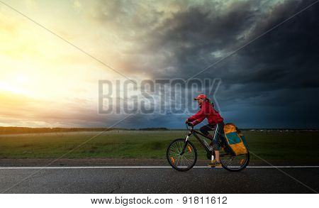 Lady hiker riding loaded bicycle on a paved asphalt road with dark storm clouds on the background