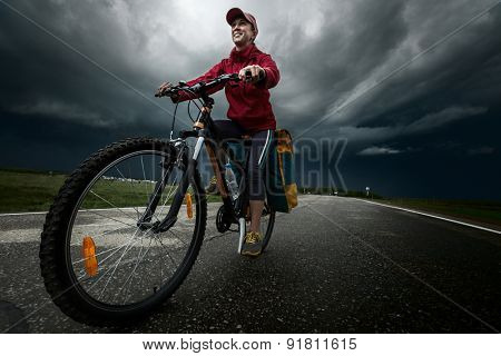 Lady hiker riding loaded bicycle on the paved asphalt road with stormy clouds on the background