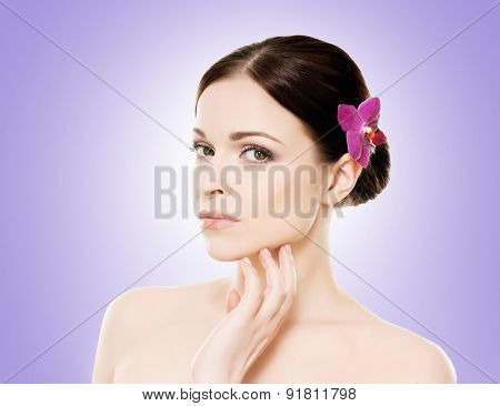 Beautiful face of a young and healthy girl with an orchid flower in her hair over blue background