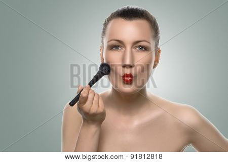 Woman Putting Makeup On Face With Pouting Lips