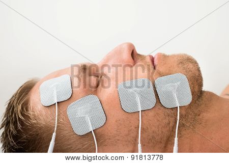 Man Closing Eyes With Electrodes On Face
