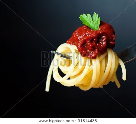 Delicious spaghetti on fork close-up. black background