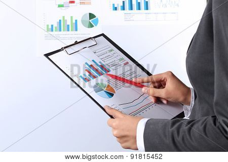 Young Businesswoman Showing Graphs By Pen