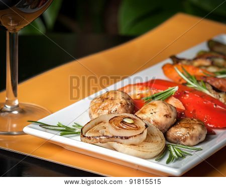 Grilled vegetables on yellow and black background with a glass of wine