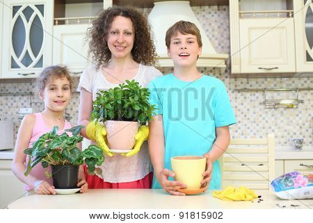 Portrait of a happy mother with son and daughter with houseplants in the kitchen