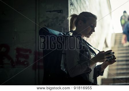 Young female backpacker in subway using camera