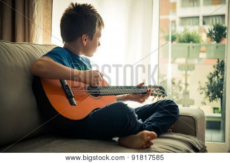 Cute boy playing guitar