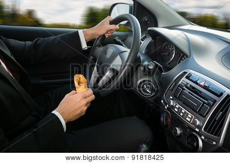 Close-up Of A Male Holding Snack While Driving