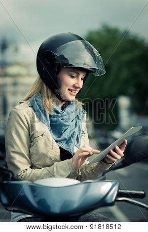 Girl sitting on her scooter with digital tablet, looking direction on GPS