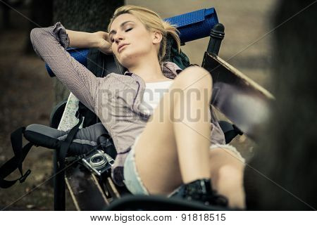 Young female backpacker resting on  a bench