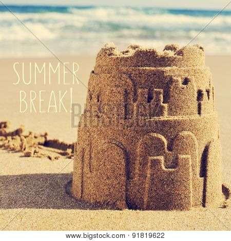 a sandcastle on the sand of a beach and the text summer break