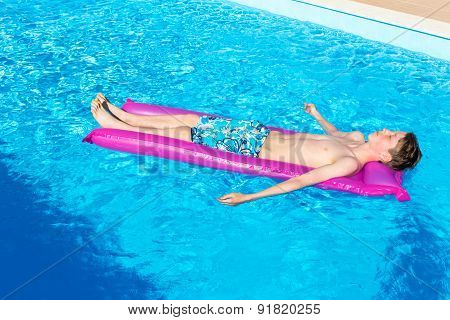 Teenage boy lying on air mattress in swimming pool