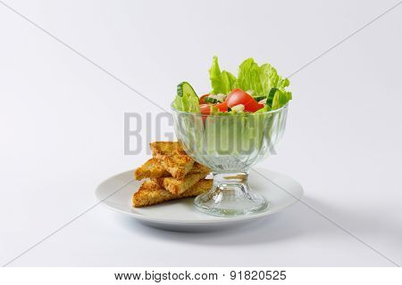 glass of mixed vegetable salad and slices of roasted toast bread on white plate