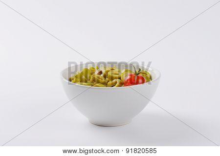 bowl of sliced green olives on white background